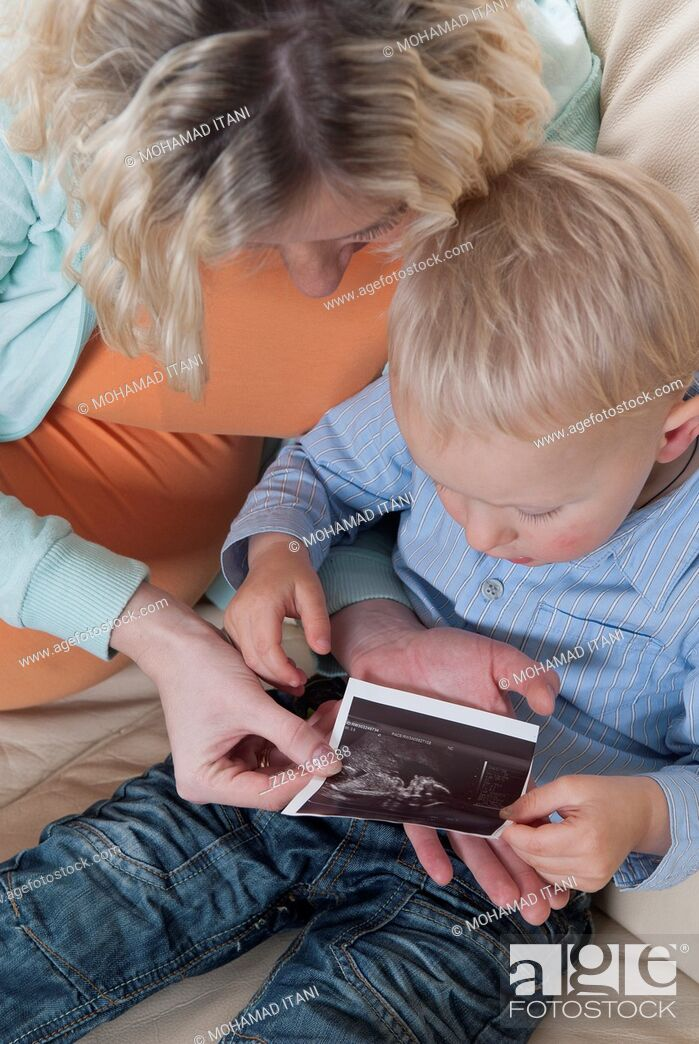 Stock Photo: Pregnant woman showing baby scan photo to toddler son.