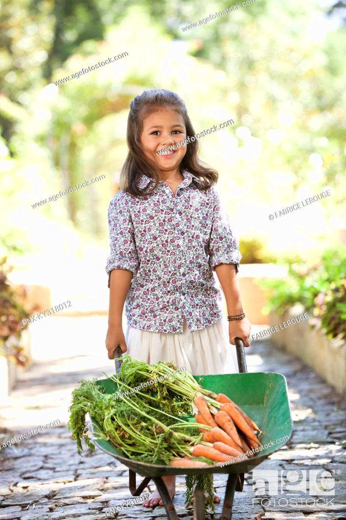 Stock Photo: Cute girl pushing a wheelbarrow filled with carrots.