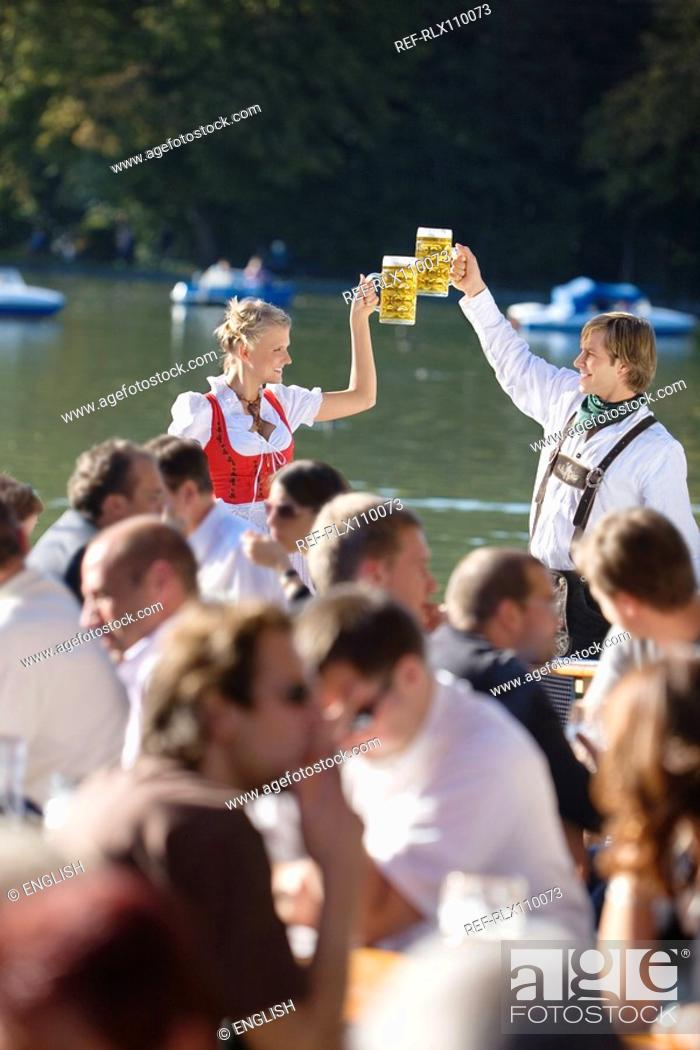 Stock Photo: Young couple in traditional Bavarian outfit, toasting with beer glasses in crowd.