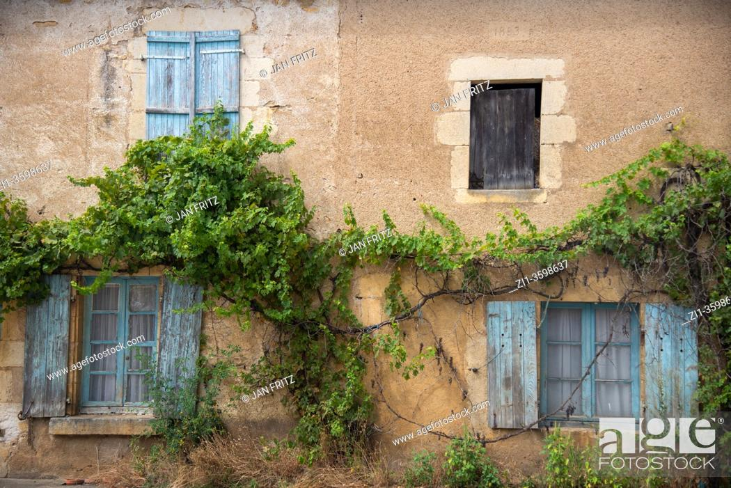Photo de stock: window with old blue shutters in France.