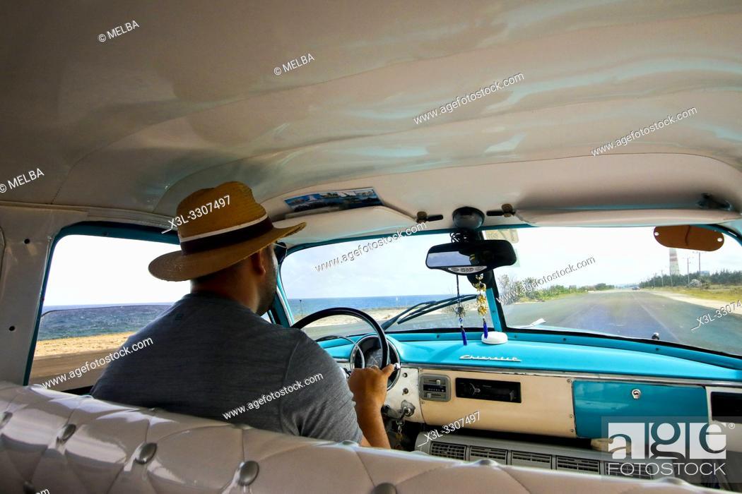 Stock Photo: Ciuban driver ina vintage car in Cuba.