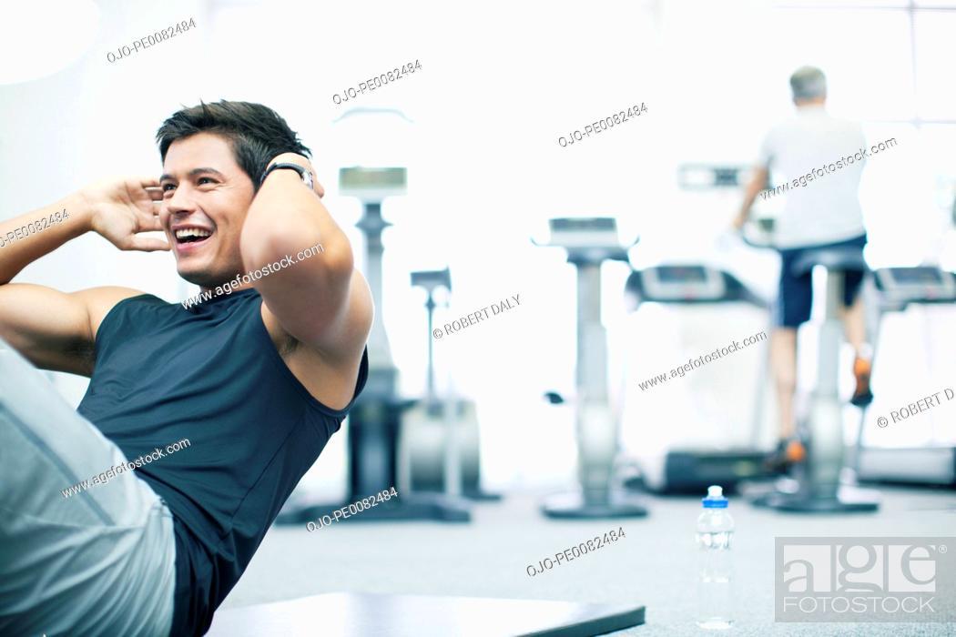 Stock Photo: Smiling man doing sit-ups in gymnasium.