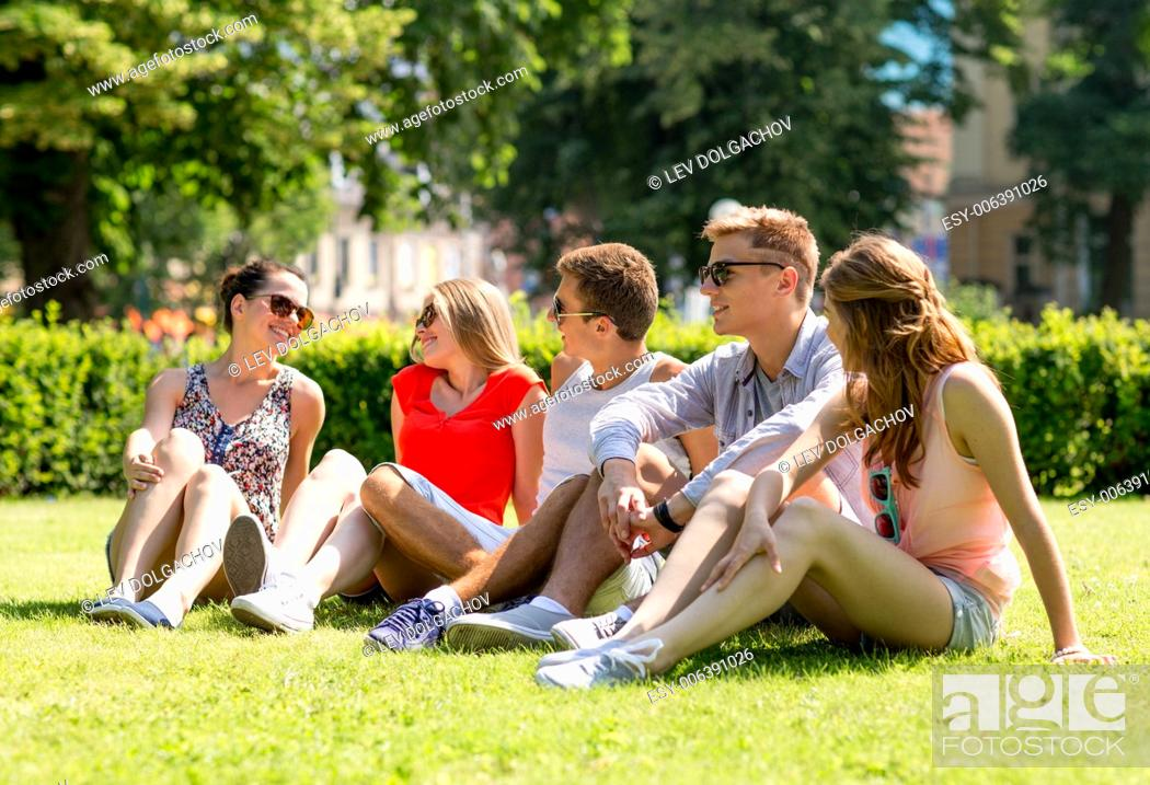 Photo de stock: friendship, leisure, summer and people concept - group of smiling friends outdoors sitting on grass in park.