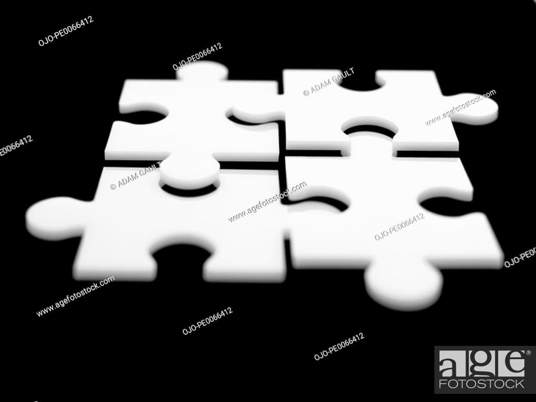 Stock Photo: Four interlocking puzzle pieces.