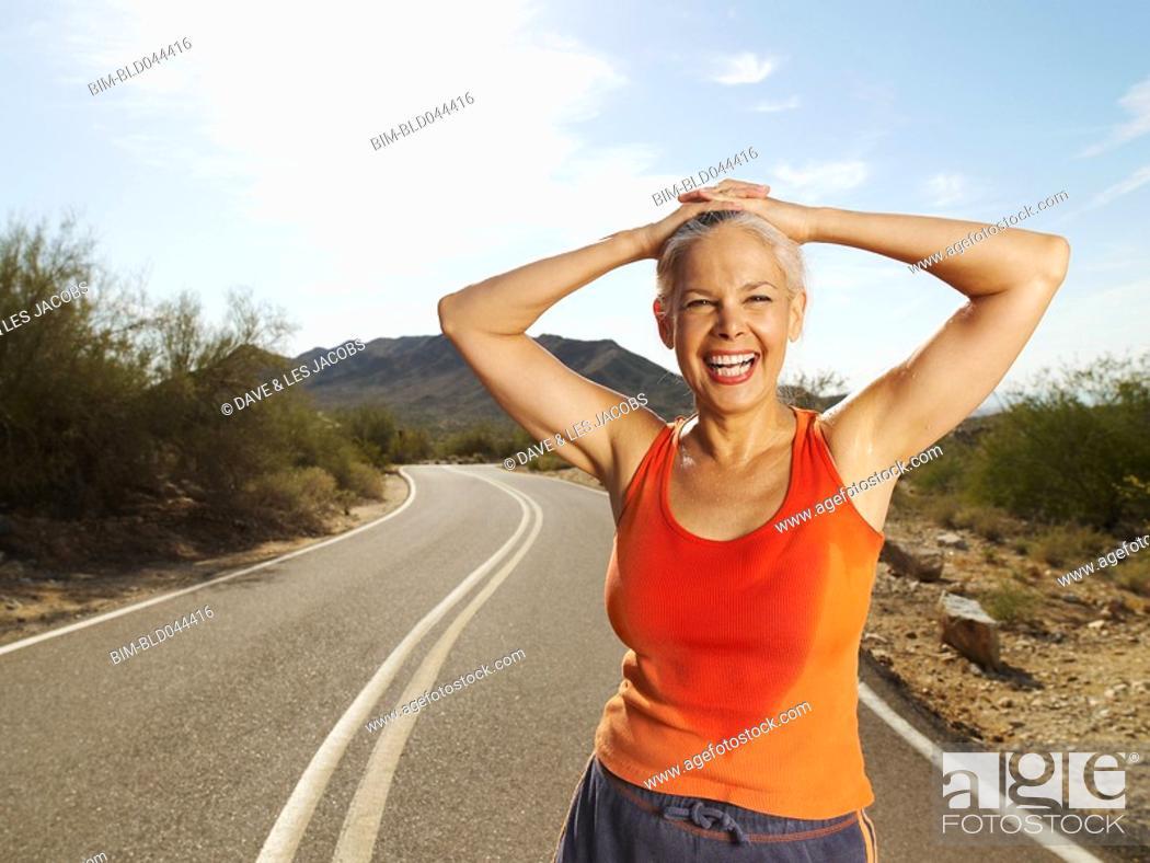Stock Photo: Senior Hispanic woman taking break from jogging.