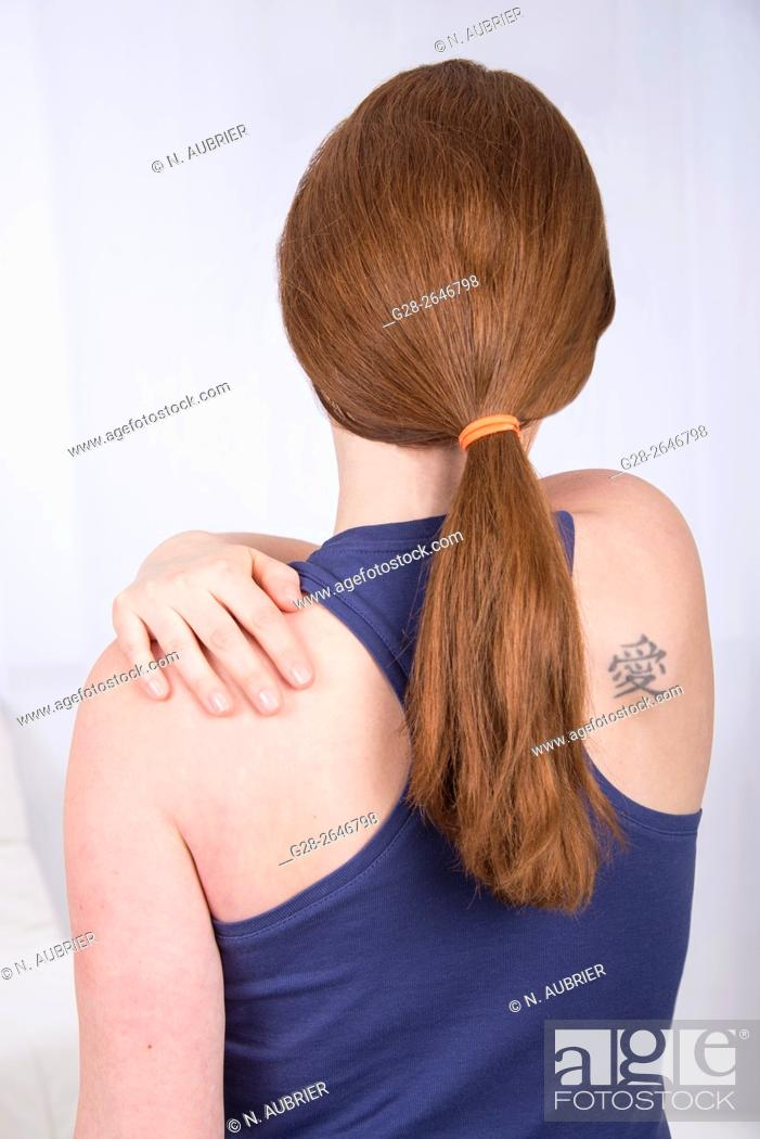 Stock Photo: Young woman suffering from her shoulder and holding it.