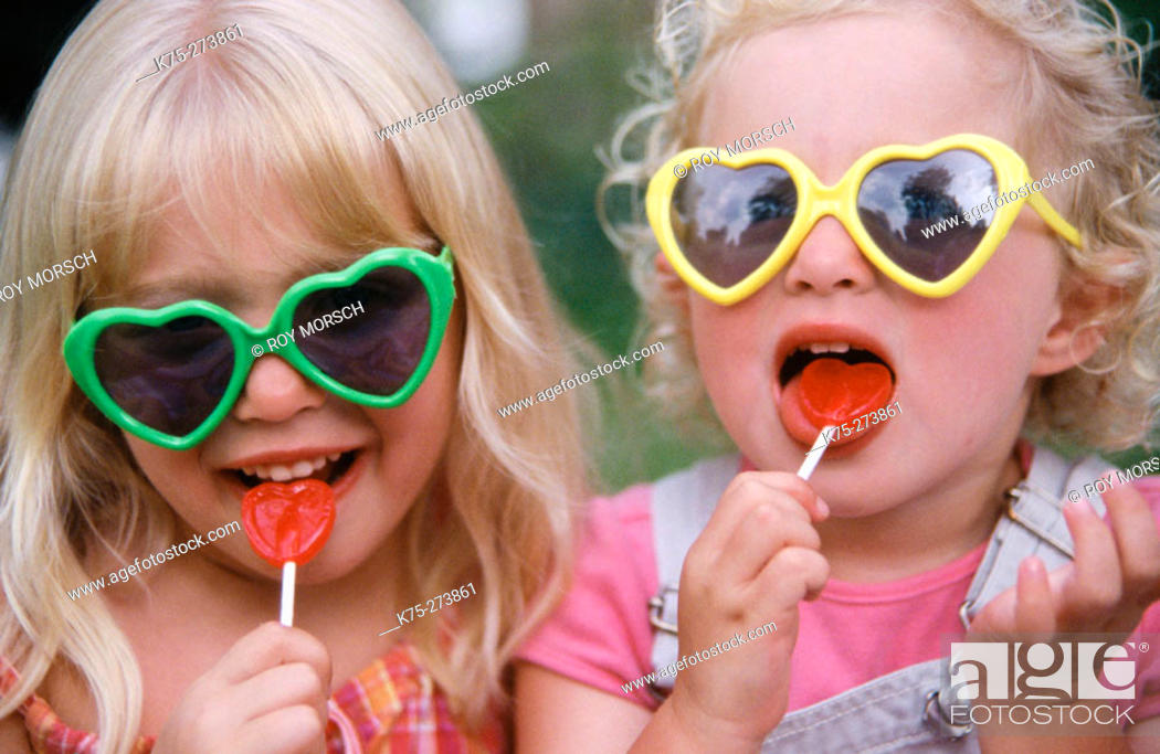 Stock Photo: sisters with heart sunglasses and lollipops.