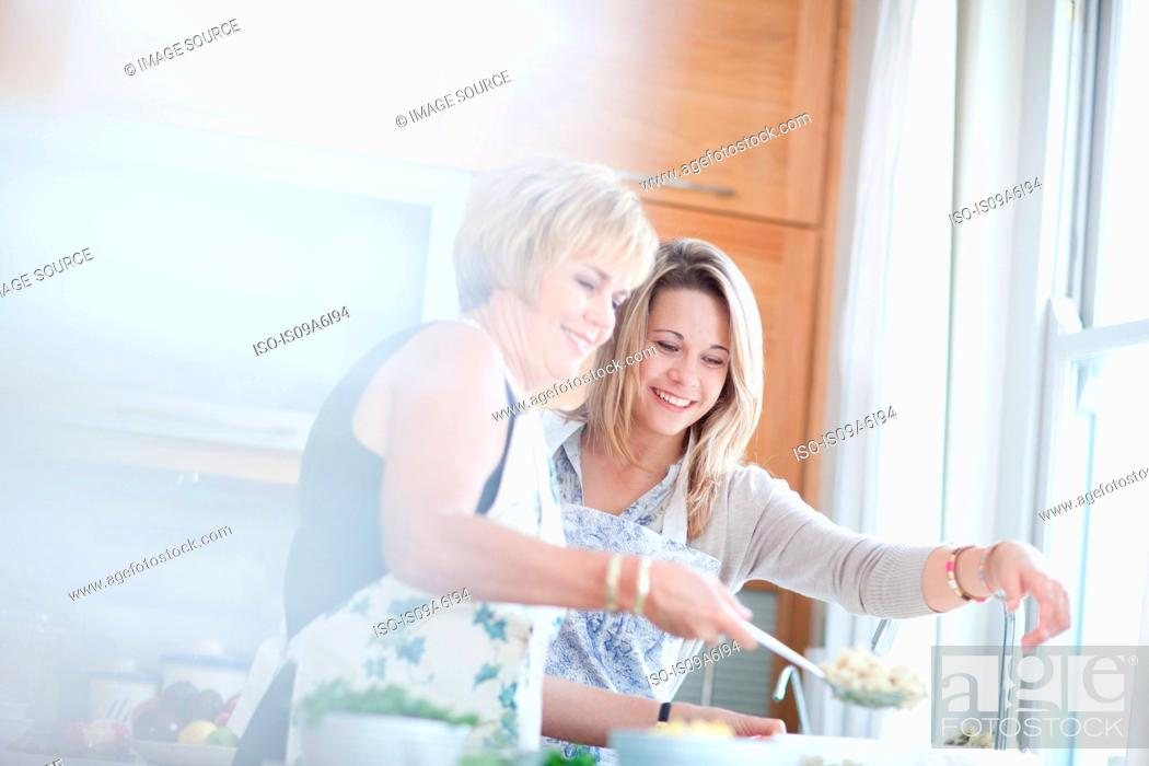 Stock Photo: Mother and daughter cooking in kitchen.