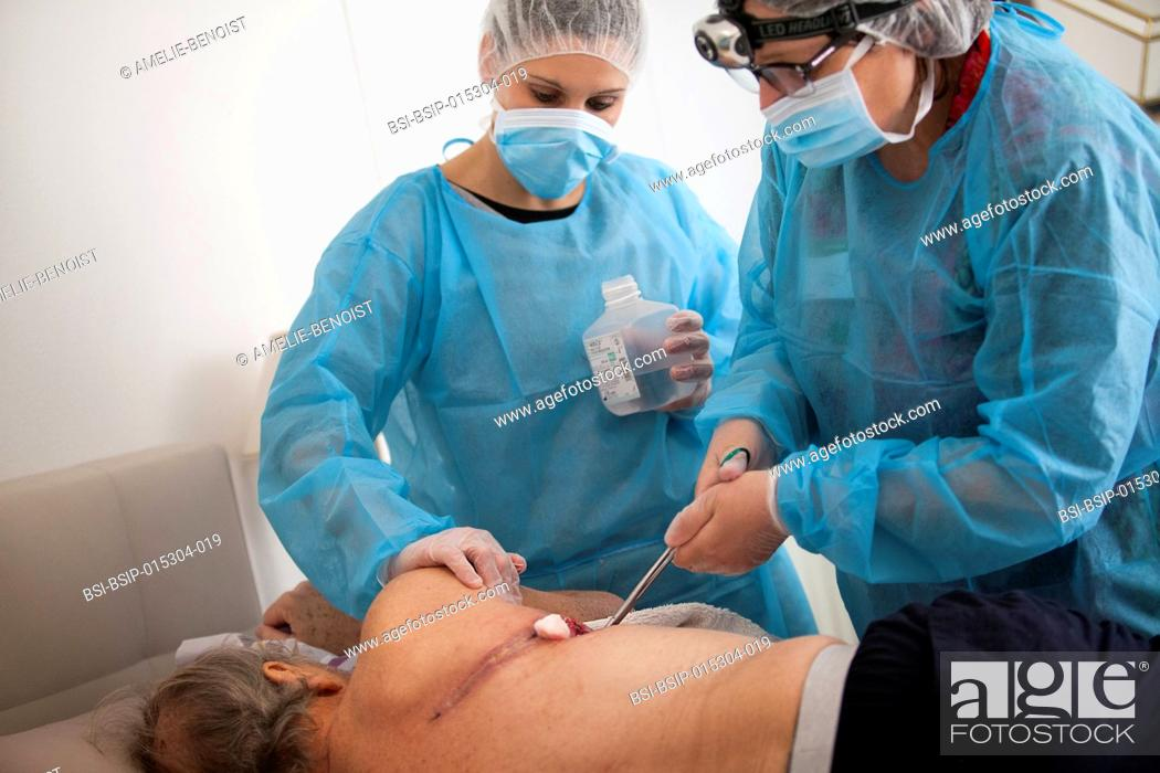 Stock Photo: Reportage on a home health care service in Savoie, France. A nurse and auxiliary nurse place a VAC therapy dressing on a pulmonectomy.