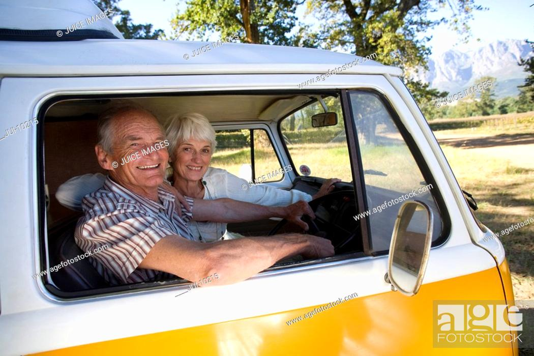 Stock Photo: Senior couple in camper van, smiling, portrait.