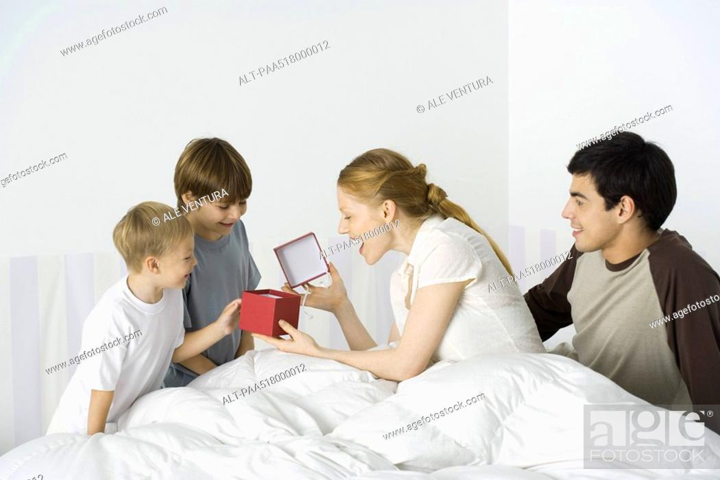 Stock Photo: Two boys giving mother present in bed, husband watching.