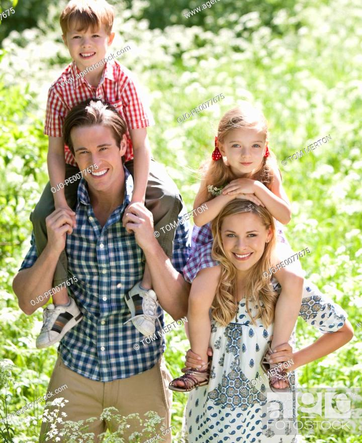 Stock Photo: Parents holding children on shoulders in park.
