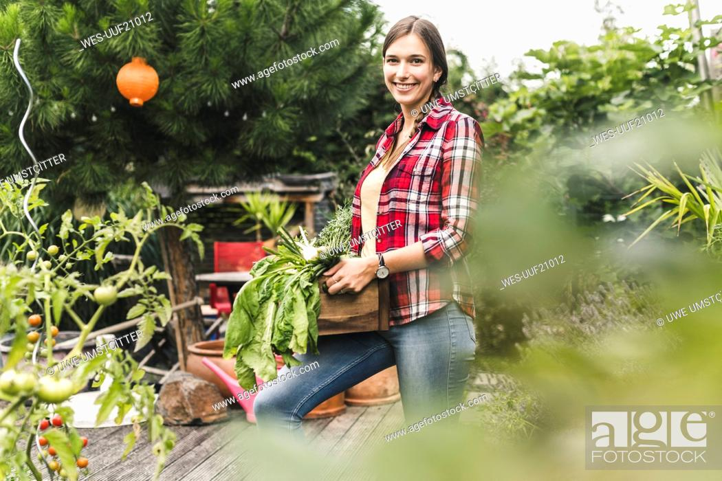 Imagen: Smiling young woman carrying crate while standing in vegetable garden.