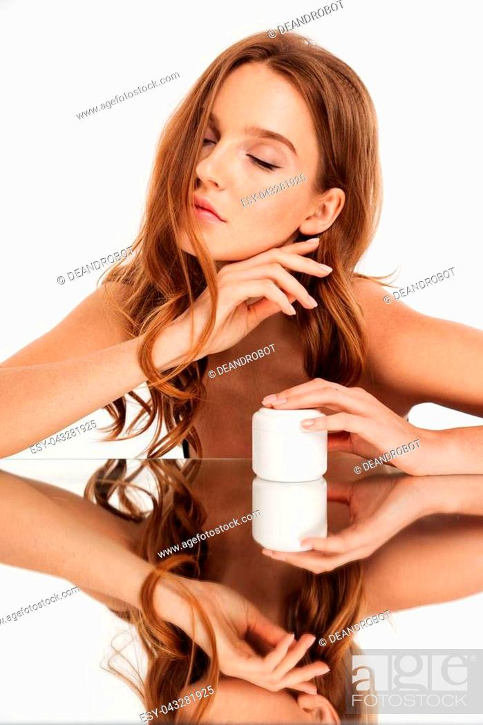 Stock Photo: Vertical Beauty portrait of ginger woman with long hair and closed eye sitting by the mirror table with body cream over grey background.