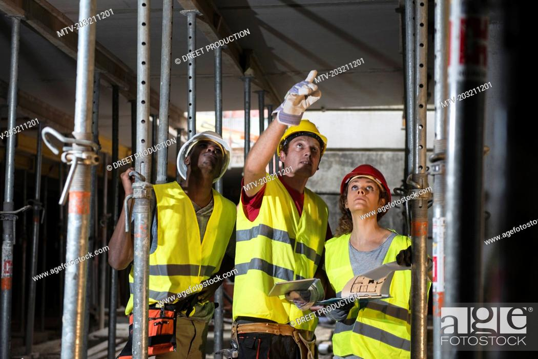 Stock Photo: Construction workers with digital tablet and architectural plan at building site.