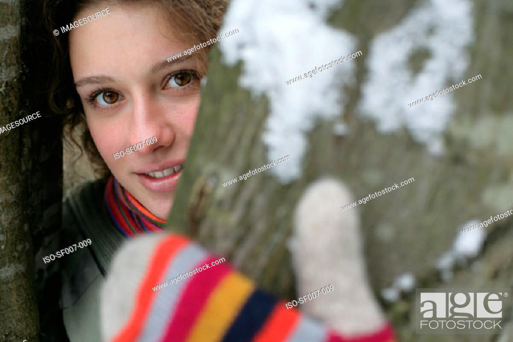 Stock Photo: Woman in gloves behind a tree.