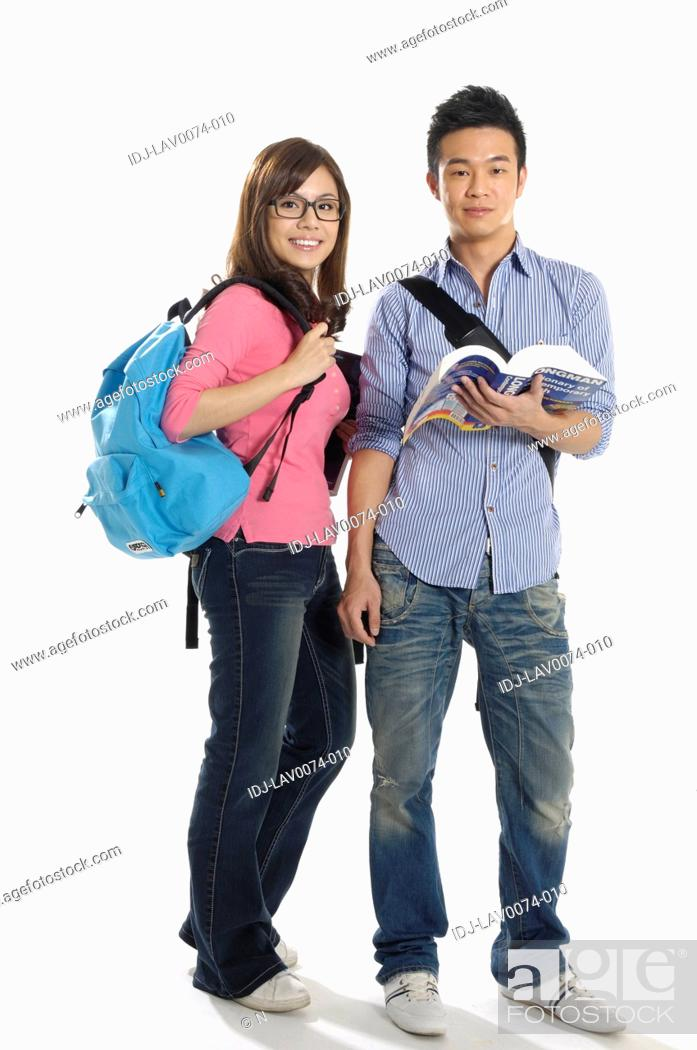 Stock Photo: University students standing together with a book.