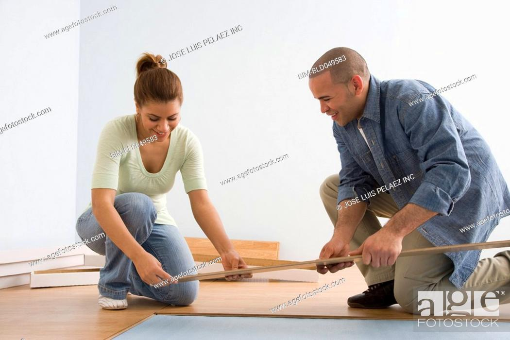 Stock Photo: African American couple installing flooring.