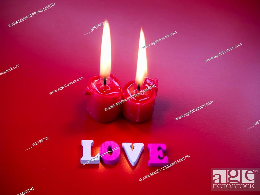 Stock Photo: Concept of love Red candles lit and the word love with a red background.