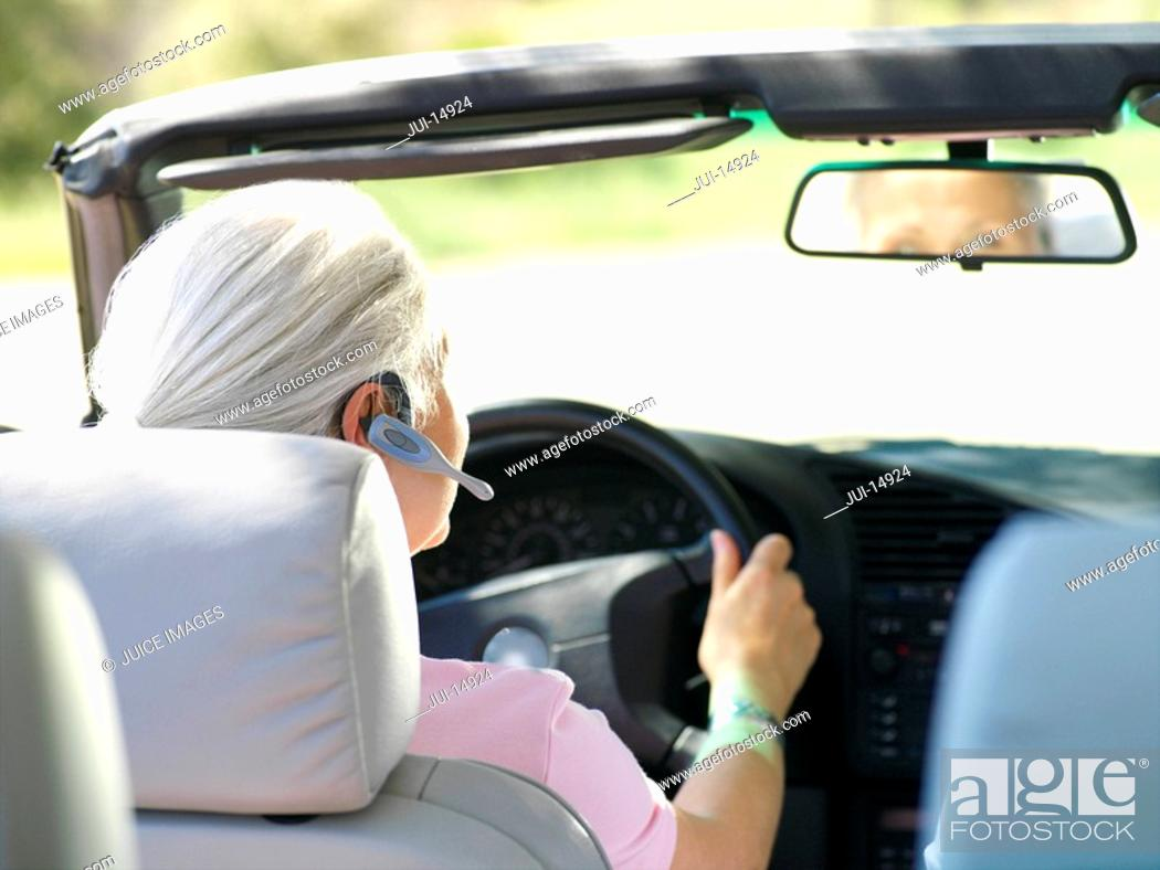 Stock Photo: Woman with hands-free device in car, rear view.