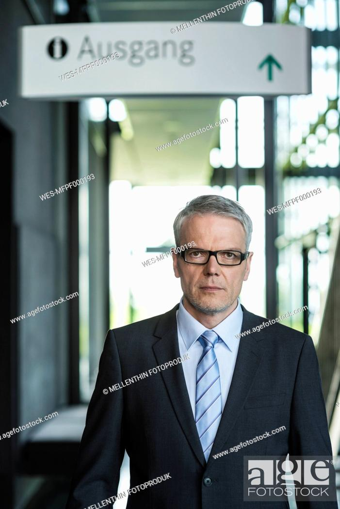 Stock Photo: Germany, Stuttgart, Businessman standing in office building, portrait.