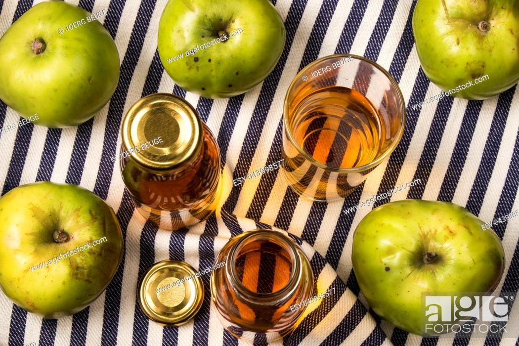 Stock Photo: home made apple juice from an old british apple variety, bramley in a glass and bottle.