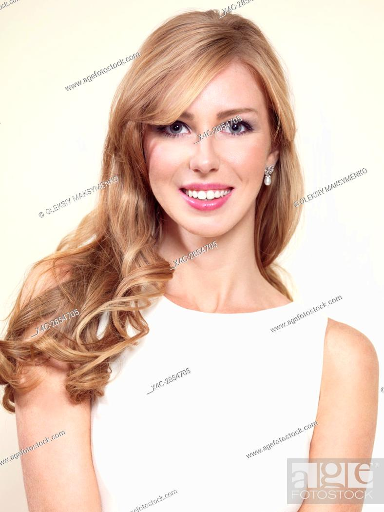 Stock Photo: Portrait of a smiling caucasian woman with long blond hair in her thirties isolated on light background.