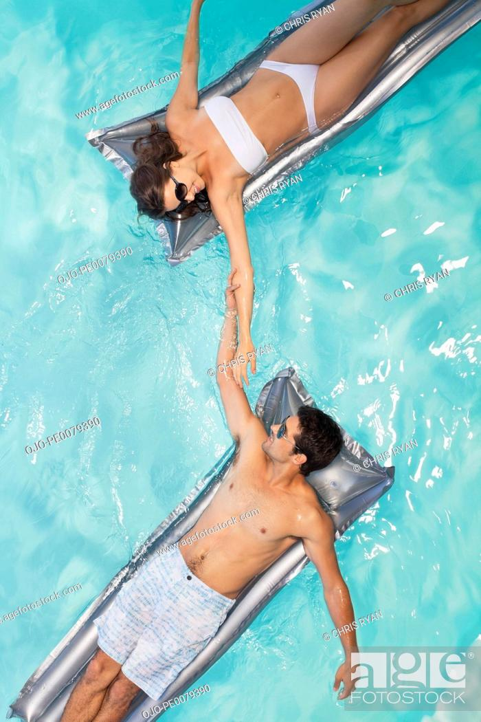 Stock Photo: Couple floating in swimming pool holding hands.