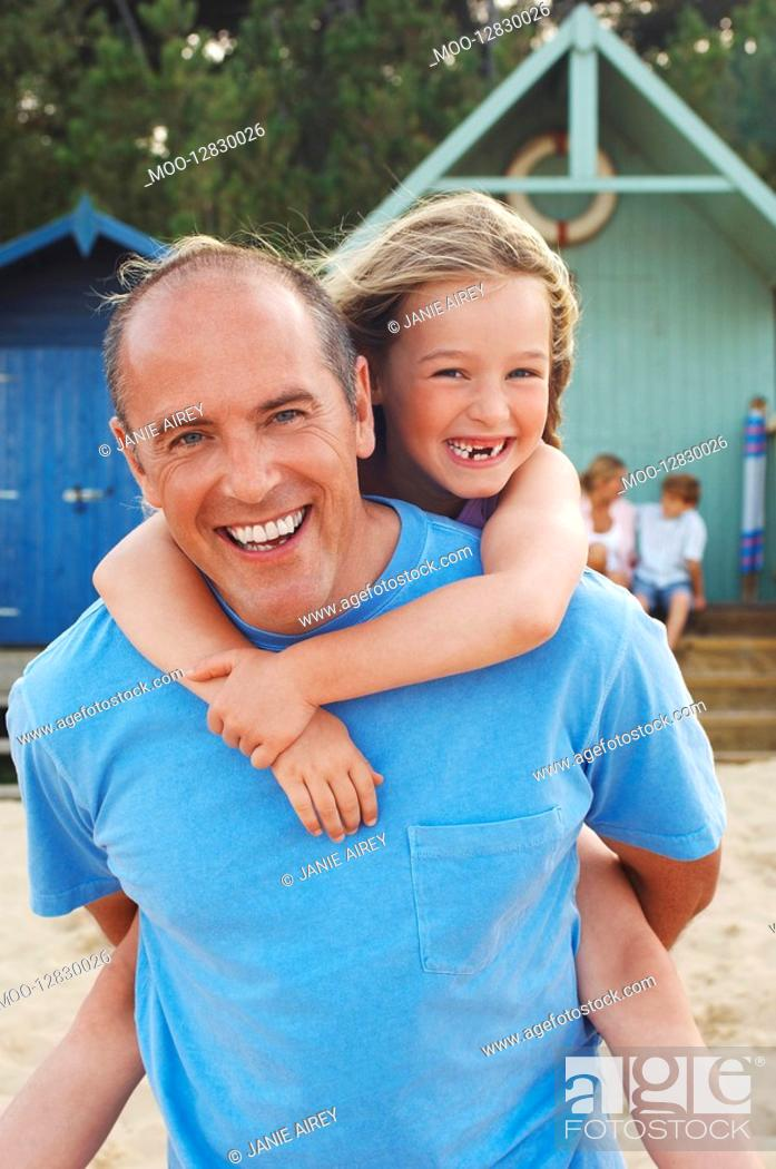 Stock Photo: Father giving daughter piggyback on beach portrait.