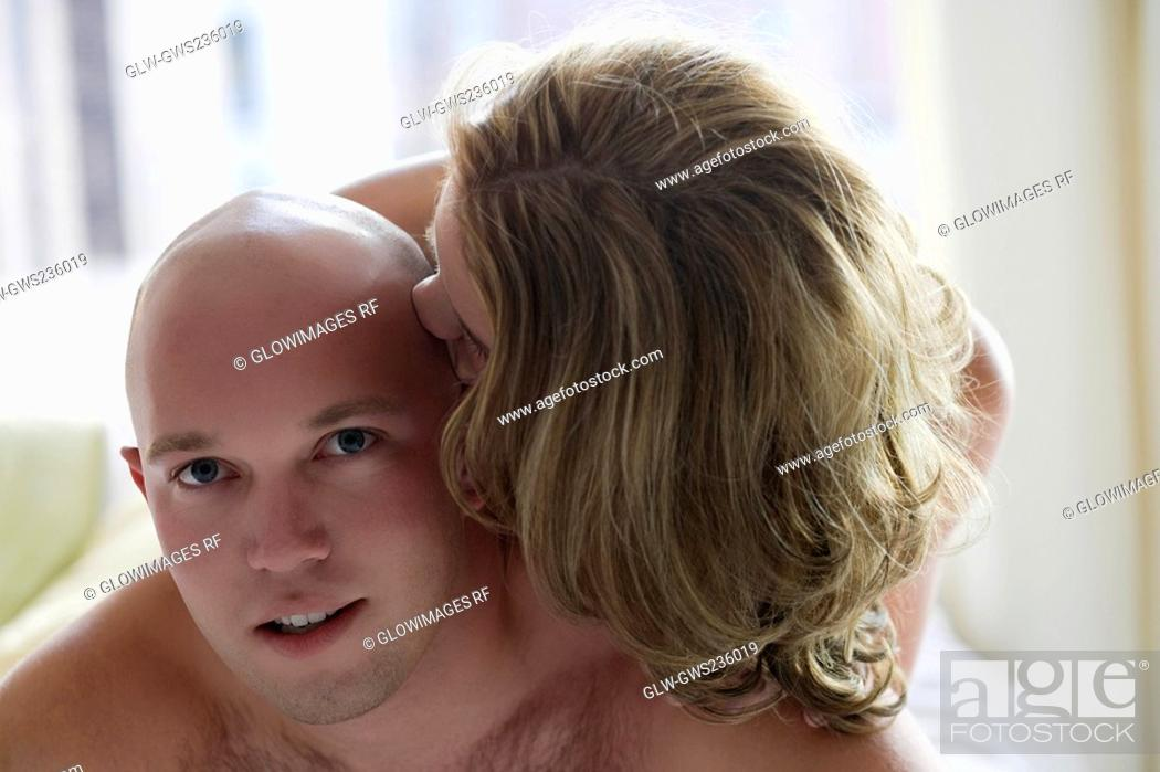 Stock Photo: Close-up of a young woman kissing on a young man's head.
