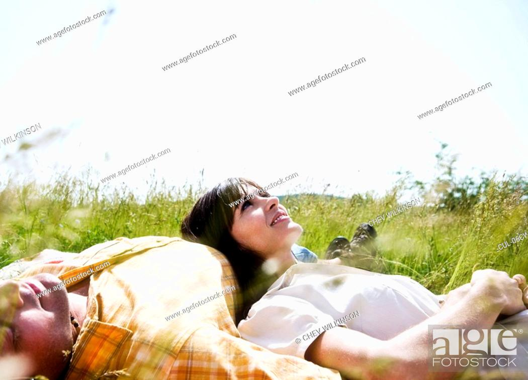 Stock Photo: Man and woman lying in grass.
