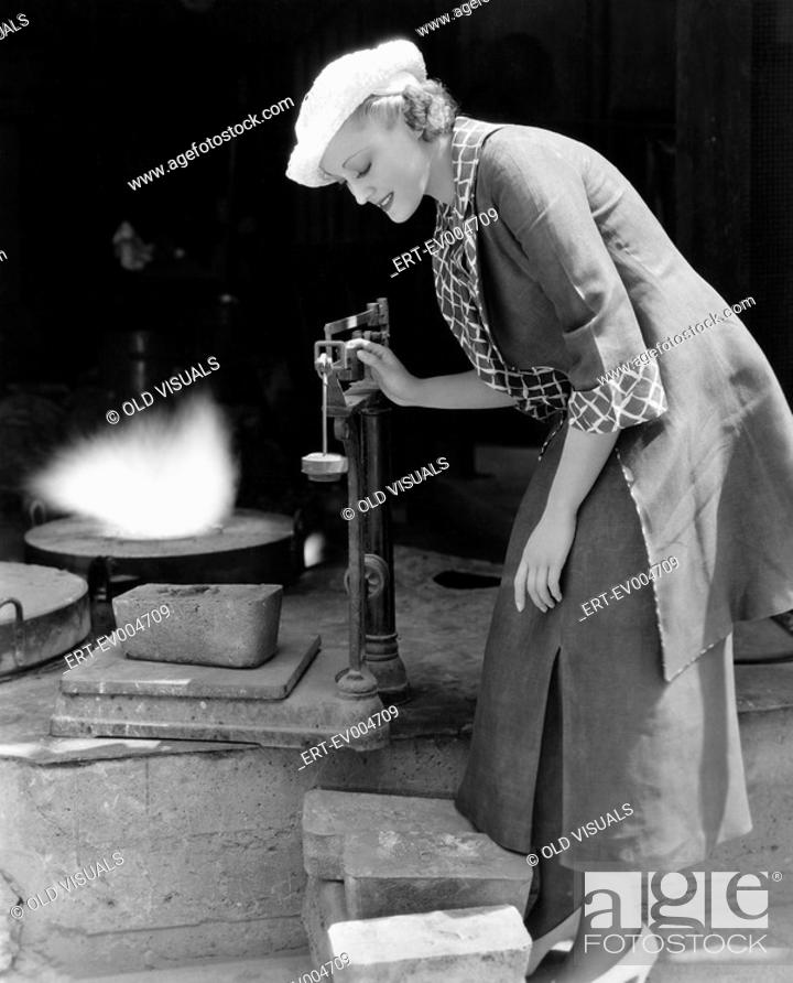 Stock Photo: Woman weighing silver outside foundry All persons depicted are not longer living and no estate exists Supplier warranties that there will be no model release.