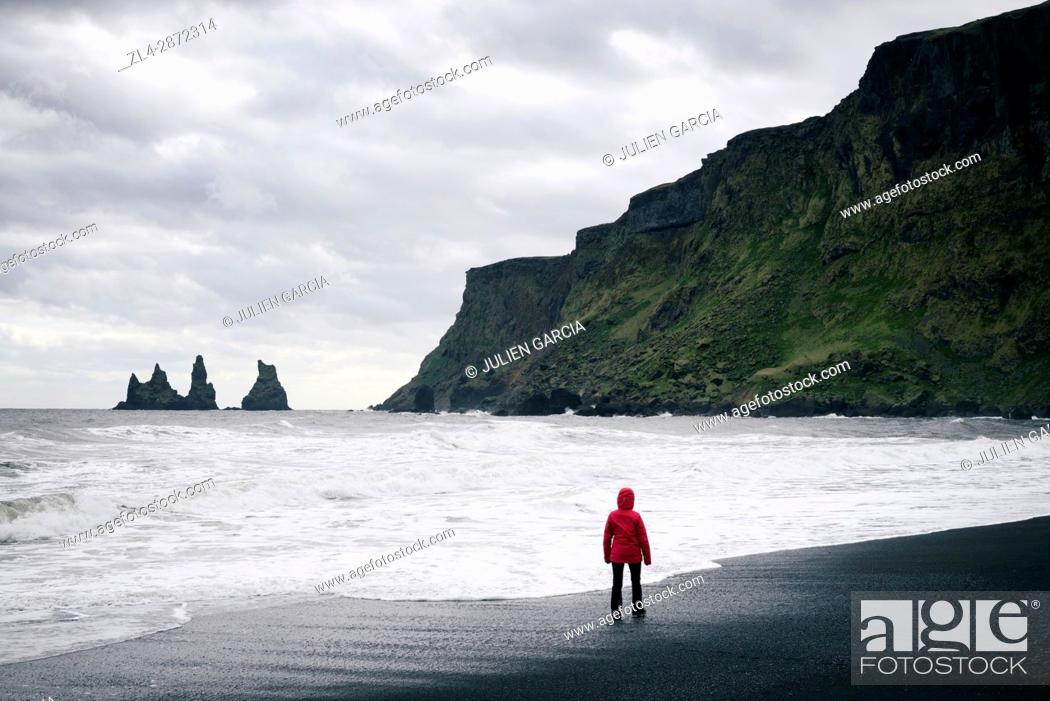 Stock Photo: Iceland, Sudurland region, Vik i Myrdal, Vik beach, woman on the black sand beach and Reynisdrangur sea stacks, Model Released.