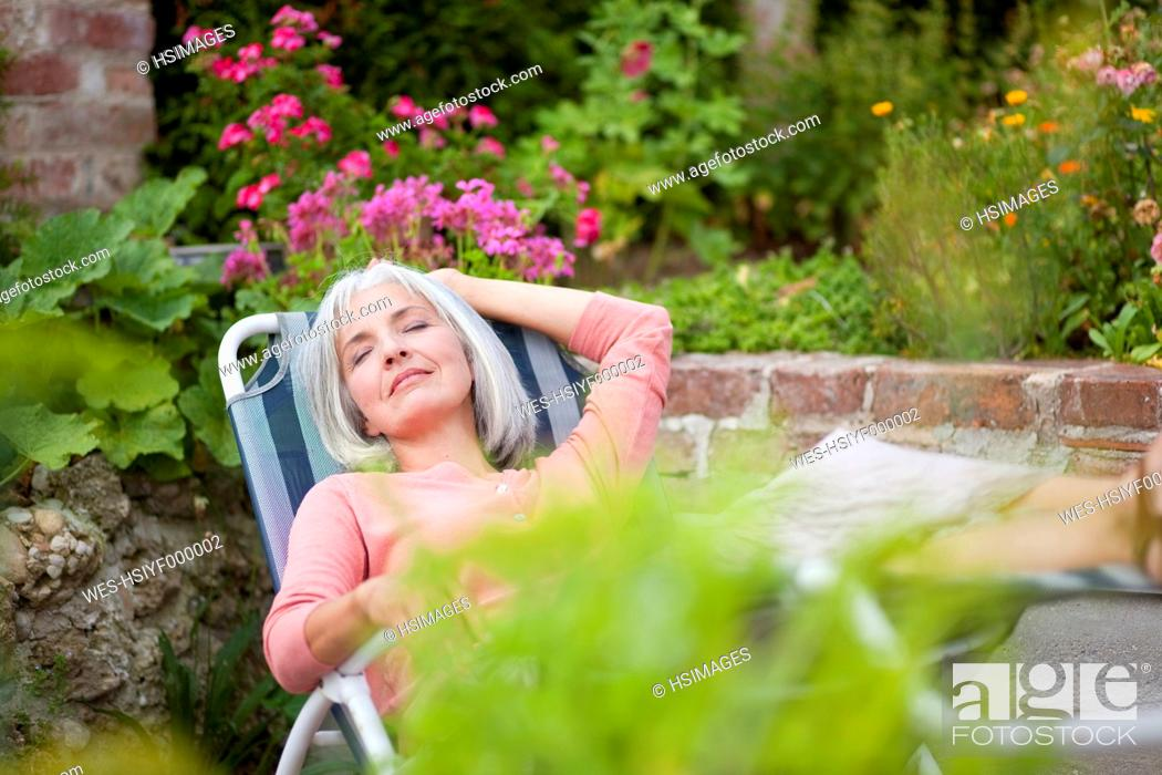 Stock Photo: Germany, Bavaria, Mature woman relaxing in garden.