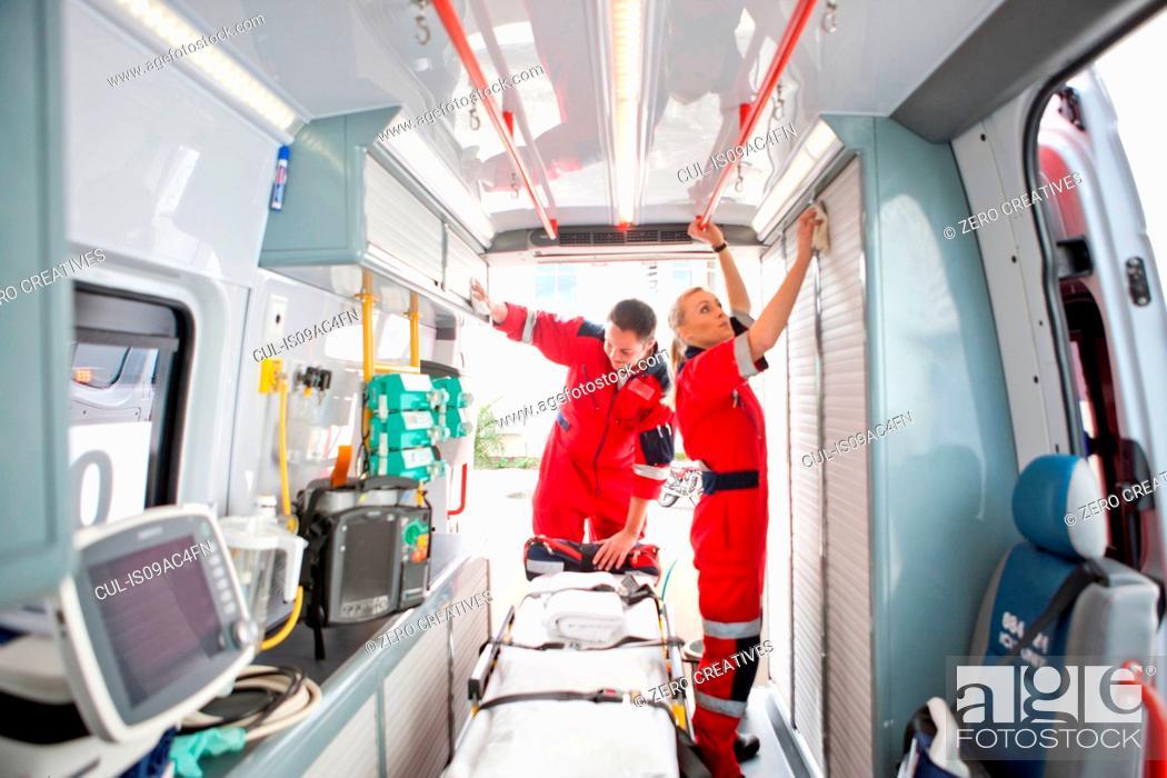 Stock Photo: Paramedics in ambulance preparing medical equipment.