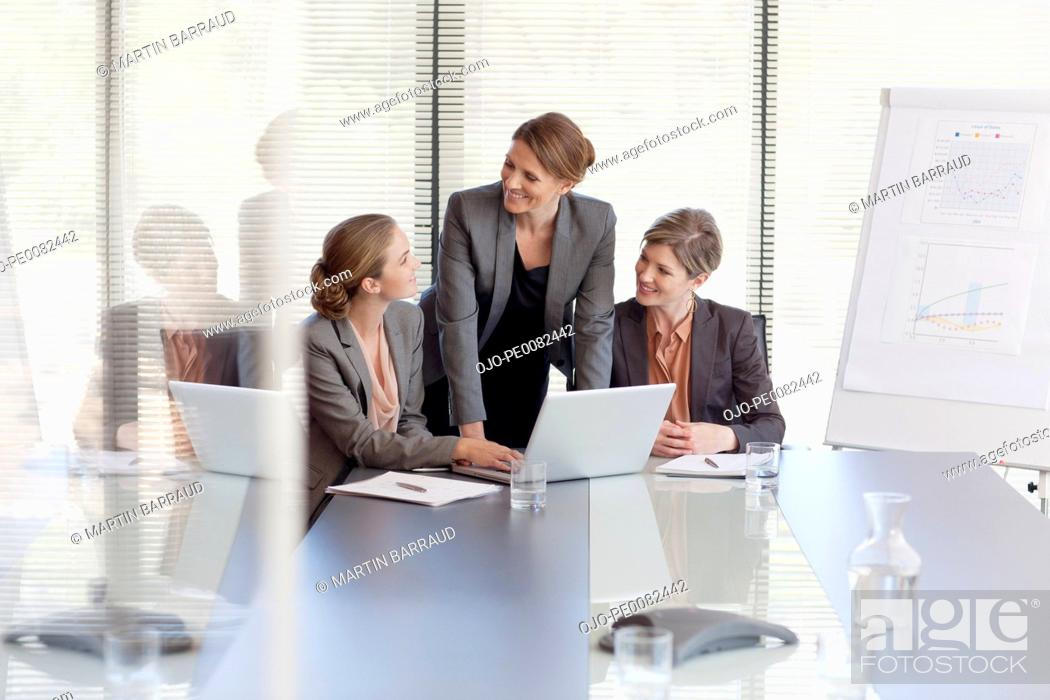 Stock Photo: Businesswomen working at laptop in conference room.