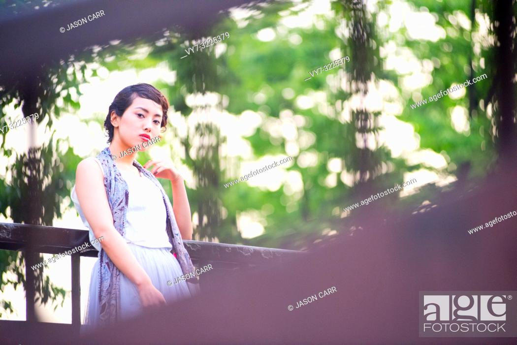 Stock Photo: Asian female model poses for pictures in the cityscape.