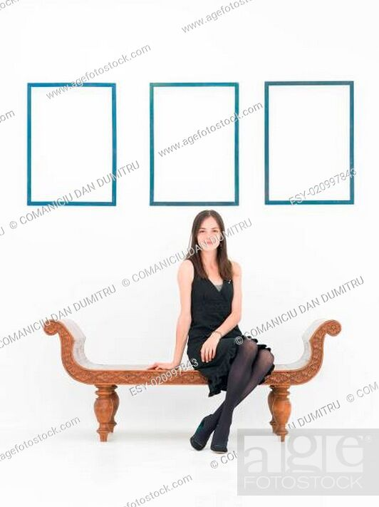 Stock Photo: young woman sitting on a bench in museum.