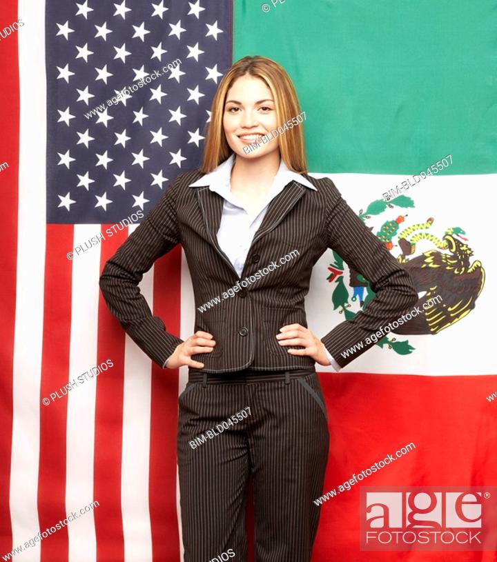 Stock Photo: Hispanic businesswoman in front of American and Mexican flags.