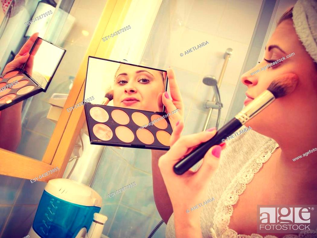 Stock Photo: Contouring face kit, visage and make up concept. Woman in bathroom applying contour bronzer on cheekbones.