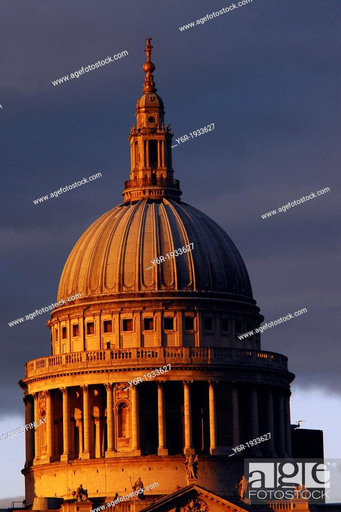 Stock Photo: The dome of St. Paul's Cathedral caught in a sudden burst of warm light breaking through dark clouds on a miserable Winter evening in London, England.