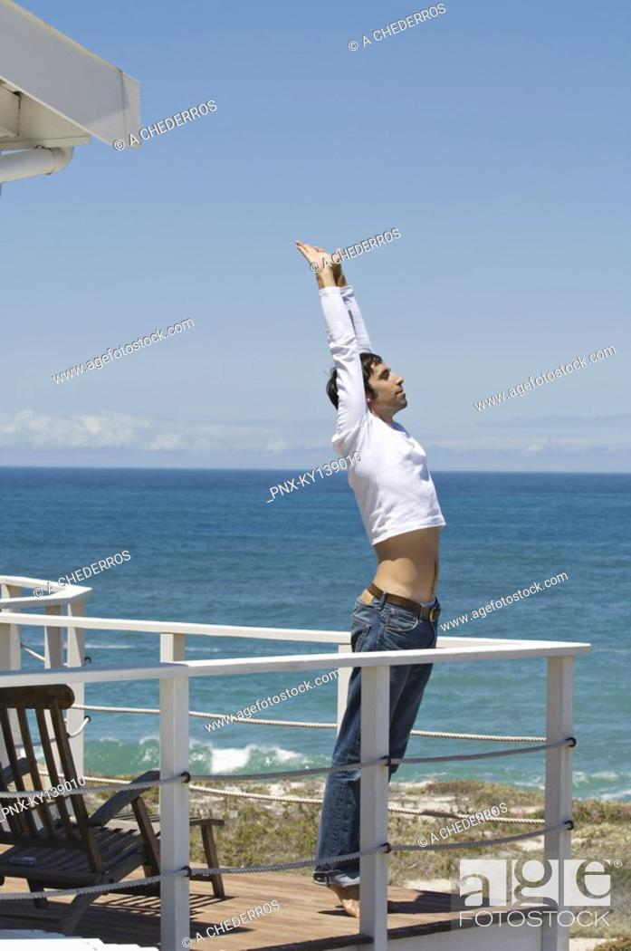 Stock Photo: Young man stretching, seafront, outdoors.