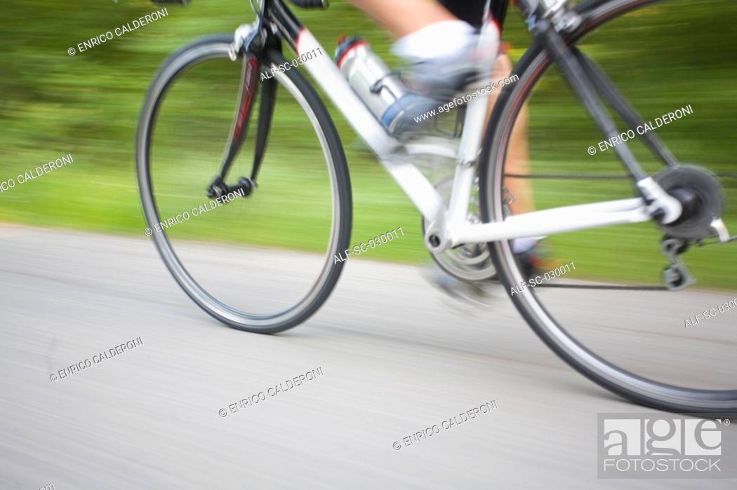 Stock Photo: Blurred motion of a cyclist pedaling.
