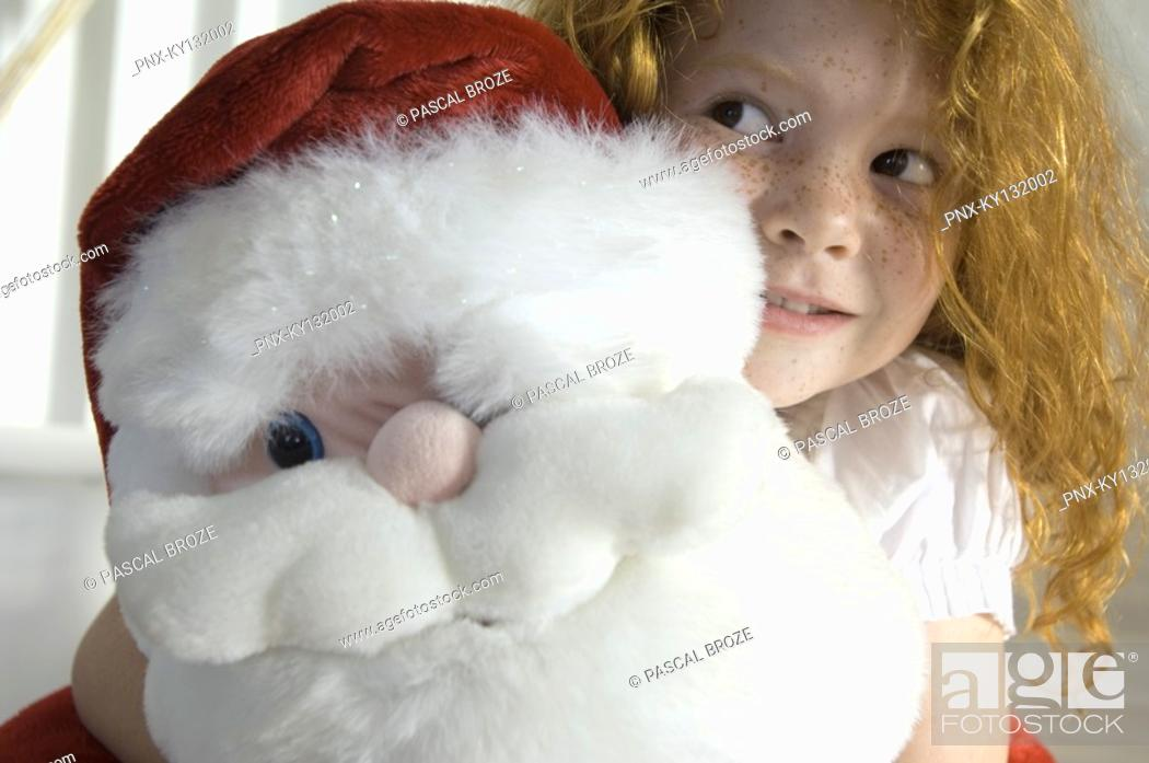Stock Photo: Christmas day, portrait of a little girl holding a cuddly toy Santa Claus, indoors.