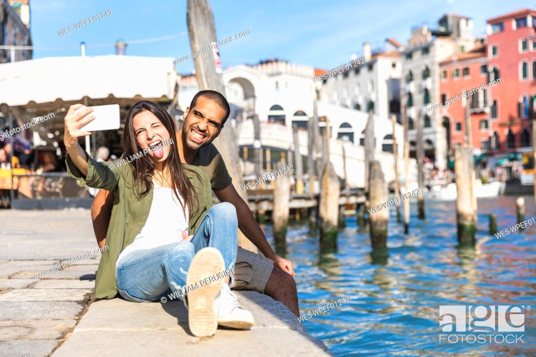Imagen: Italy, Venice, playful couple relaxing and taking a selfie with Rialto bridge in background.