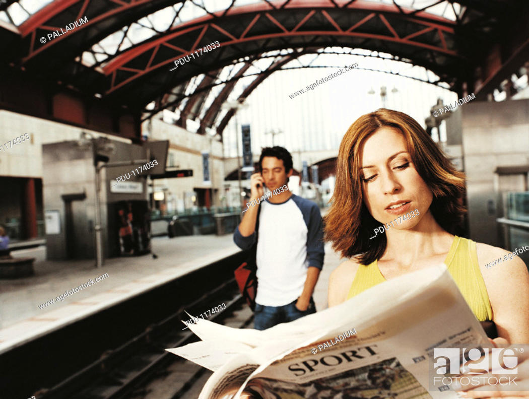 Stock Photo: Businesswoman Standing on a  Railroad Station Platform Reading a Newspaper and a Man Standing Using a Mobile Phone.