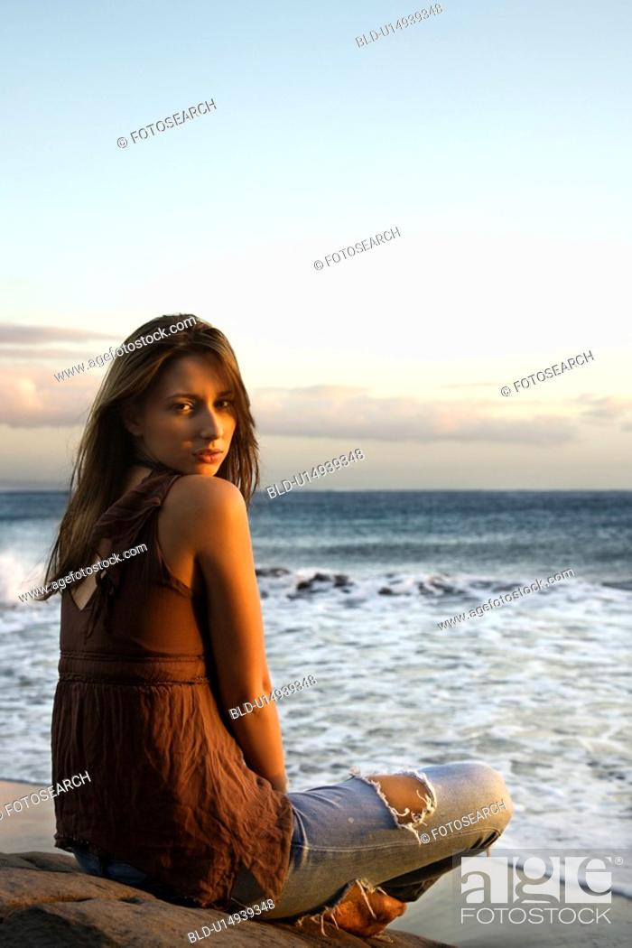 Stock Photo: Portrait of sexy young woman sitting on beach looking over her shoulder.