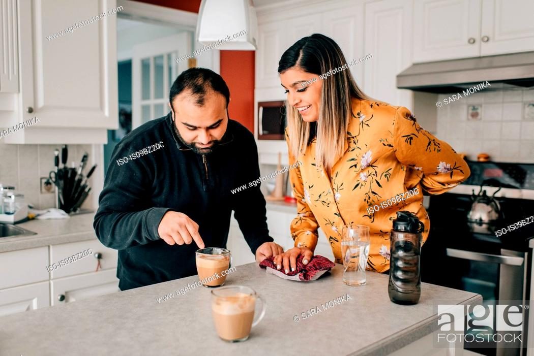 Stock Photo: Mid adult couple pointing at coffee on kitchen counter.