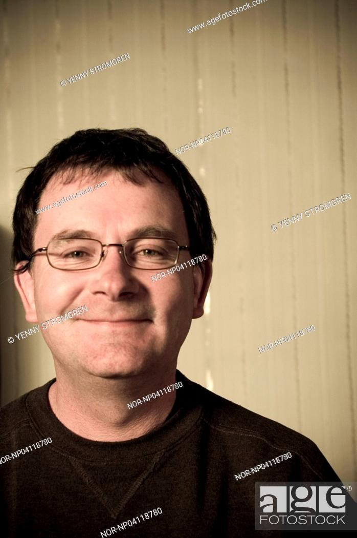 Stock Photo: Smiling man in front of wallpaper.