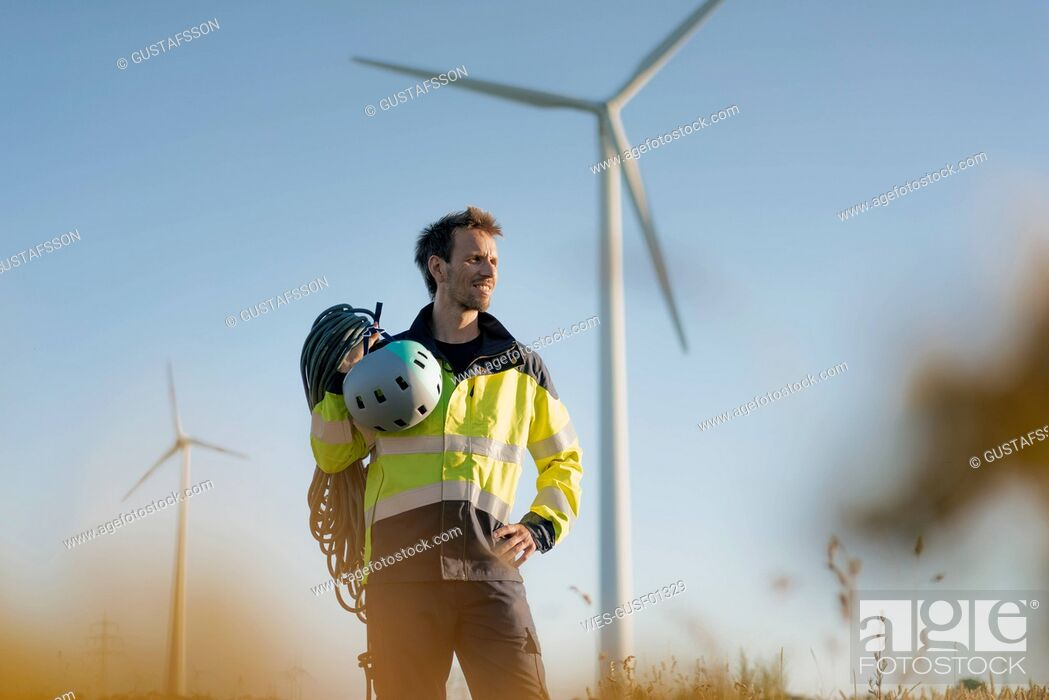 Stock Photo: Technician standing in a field at a wind farm with climbing equipment.